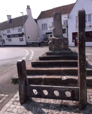 Stocks and pillory, with market cross behind